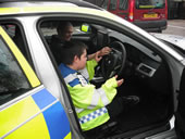 Student in driving seat of a police car