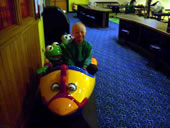 Student sat next to Kermit Frog on toy ride