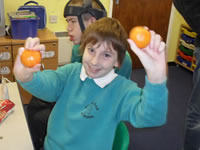 Senior pupil holding two oranges