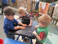 Three nursery pupils playing together around a table
