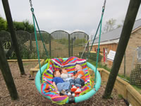 Two children on the swing outside